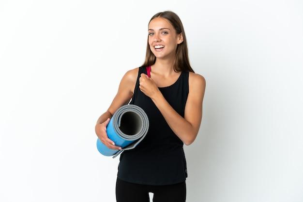 Sportvrouw die naar yogalessen gaat terwijl hij een mat over geïsoleerde witte achtergrond houdt die een overwinning viert