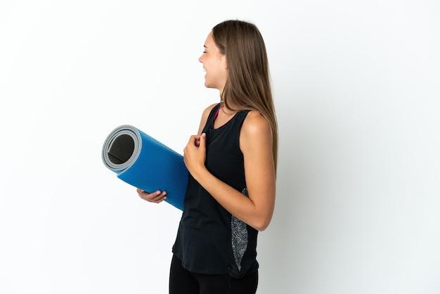 Sportvrouw die naar yogalessen gaat terwijl hij een mat over geïsoleerde witte achtergrond houdt die in zijpositie lacht