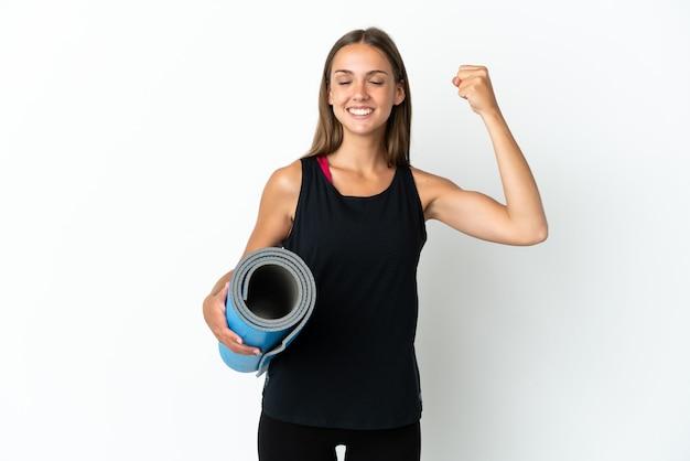Sportvrouw die naar yogalessen gaat terwijl hij een mat over geïsoleerde witte achtergrond houdt die sterk gebaar doet