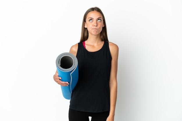 Sportvrouw die naar yogalessen gaat terwijl ze een mat over een geïsoleerde witte achtergrond houdt en omhoog kijkt