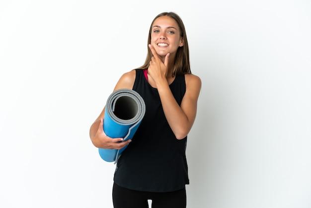 Sportvrouw die naar yogalessen gaat terwijl ze een mat vasthoudt over een geïsoleerde witte achtergrond, blij en glimlachend