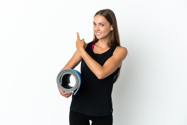 Sportvrouw die naar yogalessen gaat terwijl ze een mat vasthoudt over een geïsoleerde witte achtergrond die naar achteren wijst