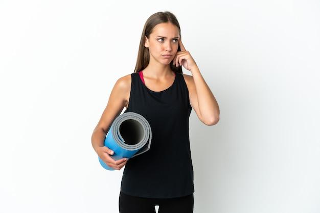 Sportvrouw die naar yogalessen gaat terwijl ze een mat vasthoudt over een geïsoleerde witte achtergrond die twijfelt en denkt