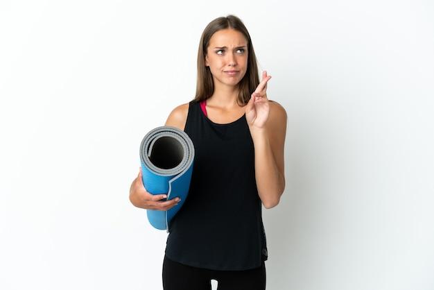 Sportvrouw die naar yogalessen gaat terwijl ze een mat vasthoudt over een geïsoleerde witte achtergrond met vingers die elkaar kruisen en het beste wensen