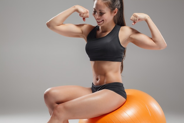 Sportvrouw die oefeningen op een fitball doet