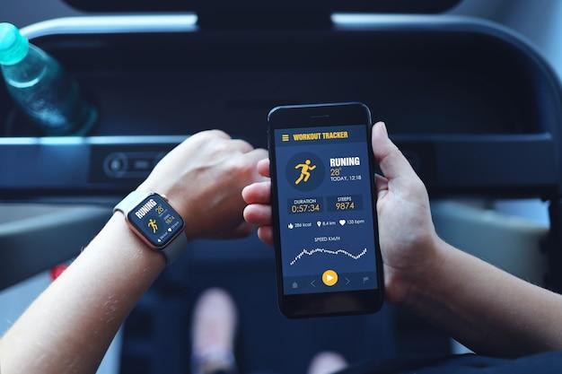 Sportvrouw die op een loopband loopt, gebruikt smartwatch om de app voor smartphonetraining te verbinden en muziek te luisteren. binnenshuis sportschool achtergrond. gezondheid sport concept