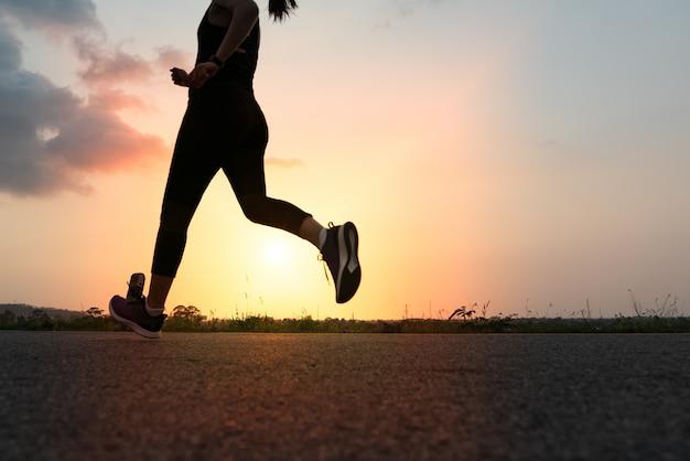 Sportvrouw die op een weg lopen. fitness vrouw training bij zonsondergang