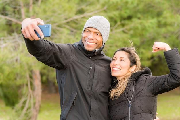Sportvrouw doet gebaar flex met één arm terwijl haar sportieve vriendje een selfie maakt. multi-etnisch paar buitenshuis.