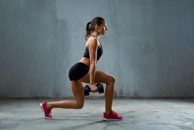 Sportvrouw doet lunges met halters