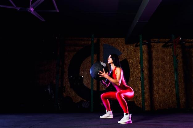 Sportvrouw doet squat oefeningen met fitness bal. wijfje die en zich met geneeskundebal bij gymnastiek uitoefenen uitrekken