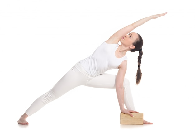 Sportvrouw doet yoga-oefeningen met een houten blok