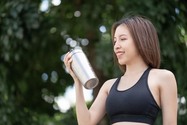 Sportvrouw drinkt proteïne shake van roestvrijstalen blender flessenschudder op natuurlijke groene achtergrond.