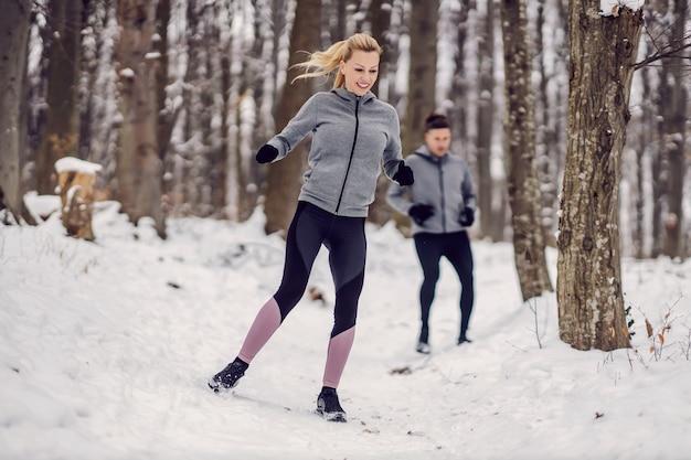 Sportvrouw haar vriend racen in bos op besneeuwde winterdag. samen fitnessen, buitenfitness, winterfitness
