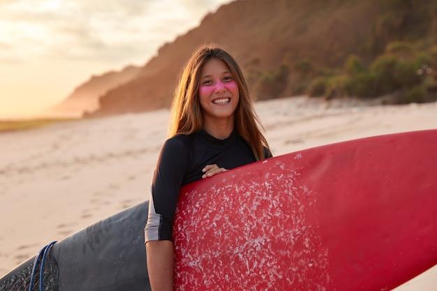 Sportvrouw heeft training op het strand, draagt paddleboard, lacht vrolijk, draagt een wetsuit, heeft een beschermend zinkmasker op het gezicht, vormt in de buurt van rif