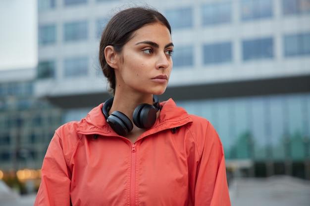 Sportvrouw heeft trainingsroutines kijkt bedachtzaam weg denkt aan het winnen van competitie luistert coole soundtracks in koptelefoon gaat video maken voor haar sportblog of geeft online les