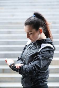 Sportvrouw het openlucht kijken haar polshorloge