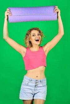 Sportvrouw houdt opgerolde oefening karemat gezondheid en lichaamsverzorging sportconcept happy fitness woman