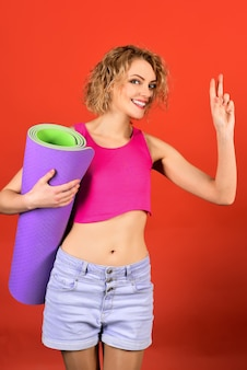 Sportvrouw houdt opgerolde oefenmat gezondheid fitness sport lifestyle concept gelukkige vrouw houdt vast