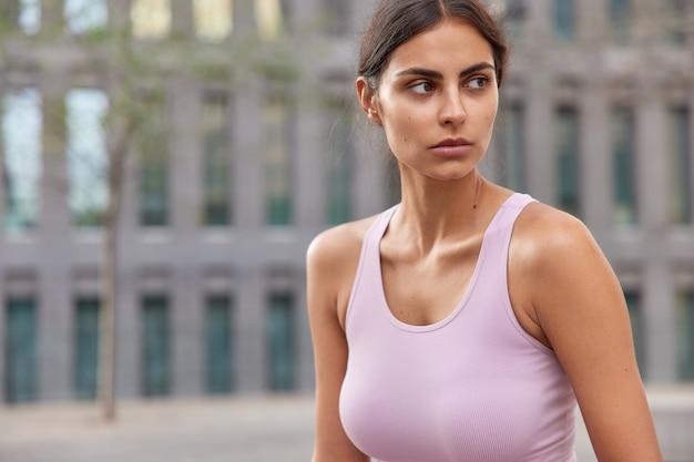 Sportvrouw in casual t-shirt kijkt peinzend weg en loopt overdag naar buiten, poseert op wazig gebouw