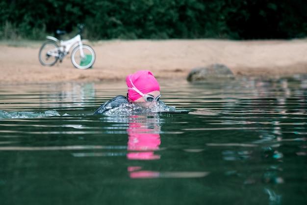 Sportvrouw in duikpak duikt in meer