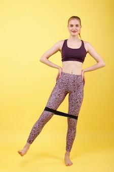Sportvrouw in lila pak schudt benen met rubberen band op gele ruimte