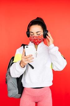 Sportvrouw in masker luisteren naar muziek met koptelefoon en slimme telefoon