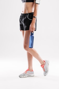 Sportvrouw in oortelefoons met fles water