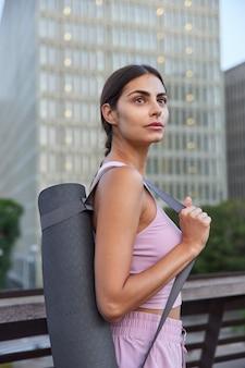 Sportvrouw in sportkleding draagt opgerolde mat op schouder en gaat oefeningen in de open lucht doen, geconcentreerde poses op stadsschrapers