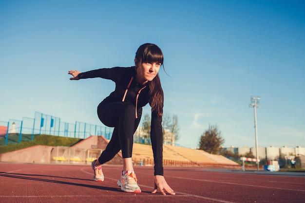 Sportvrouw in startpositie klaar om te rennen. vrouwelijke atleet die op het punt staat te sprinten in het stadion