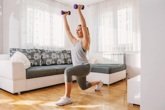 Sportvrouw in uitstekende vorm doet lunges terwijl hij thuis halters vasthoudt.