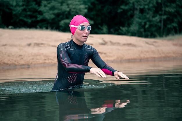Sportvrouw in wetsuit gaat het water in