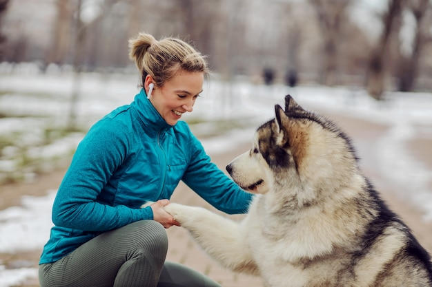 Sportvrouw leert haar hond hoe ze handen moet schudden terwijl ze in het stadspark hurkt bij sneeuwweer. honden, huisdieren, liefde, winter