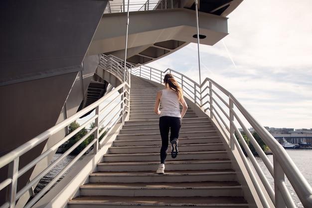 Sportvrouw loopt op de trappen van de brug