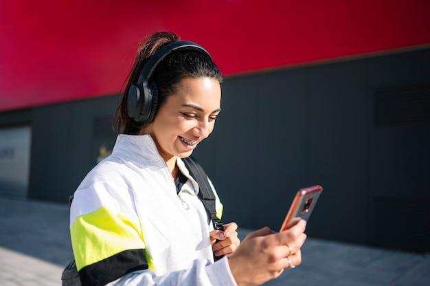 Sportvrouw luisteren naar muziek met een koptelefoon op straat lopen