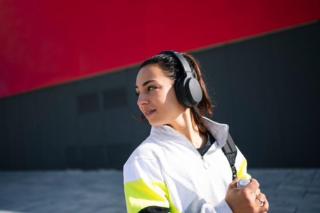 Sportvrouw luisteren naar muziek met een koptelefoon op straat
