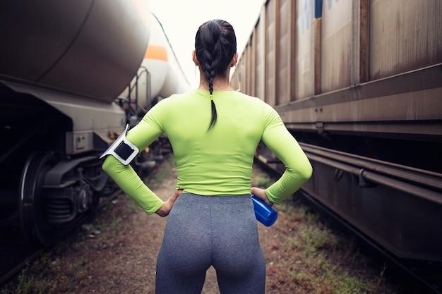 Sportvrouw met een gespierd lichaam dat voor het rennen tussen treinen op het station voorbereidingen treft