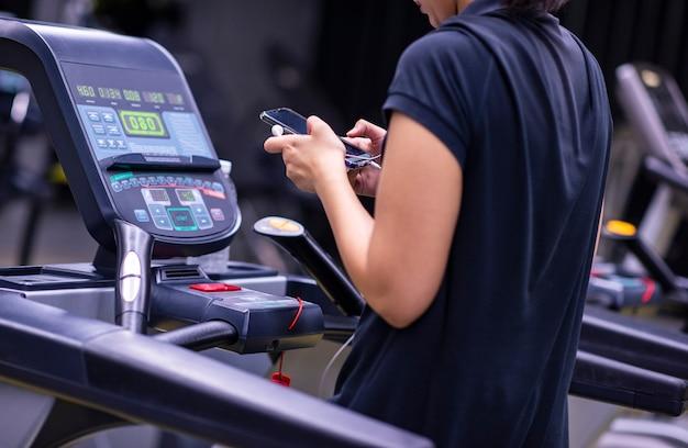 Sportvrouw met een telefoon op de tredmolen
