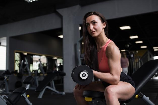Sportvrouw met gespierde armen die bicepskrullen doen, in de sportschool, kopieer ruimte