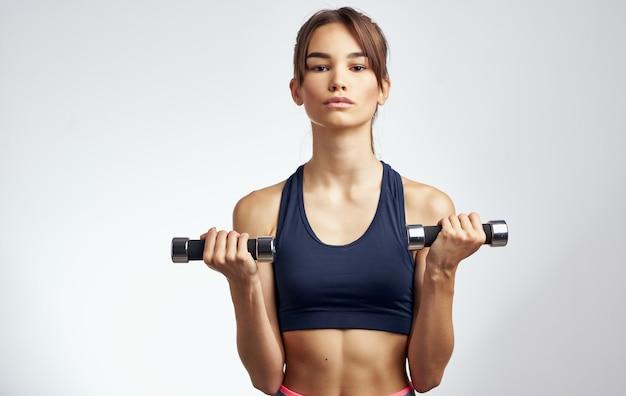 Sportvrouw met halters op een lichte achtergrond met haar handen fitness model gebaren