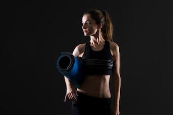 Sportvrouw met mat op donkere achtergrond