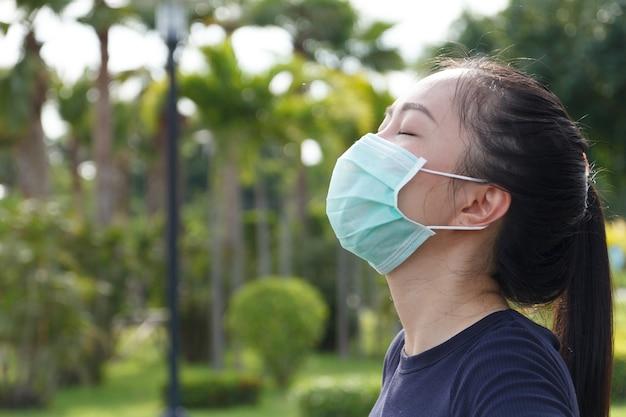 Sportvrouw met medisch beschermend masker ontspannen in het park. campagne om een beschermend masker te gebruiken tegen covid19