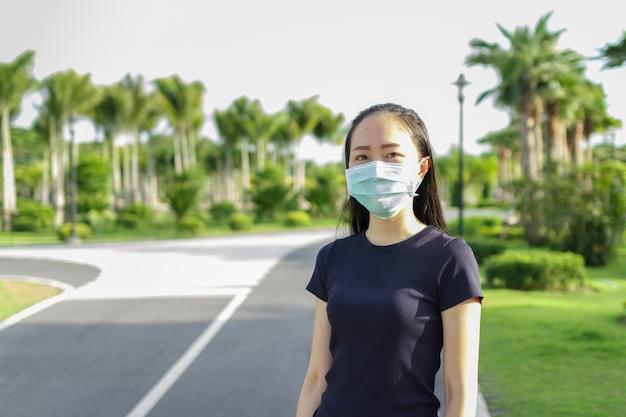 Sportvrouw met medisch beschermend masker ontspannen in het park training en beschermend masker tegen covid19
