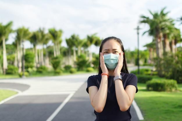Sportvrouw met medisch beschermend masker ontspannen in parkcampagne om beschermend masker te gebruiken tegen covid19