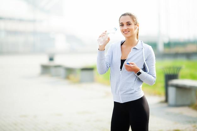 Sportvrouw na sportoefeningen in de stedelijke omgeving