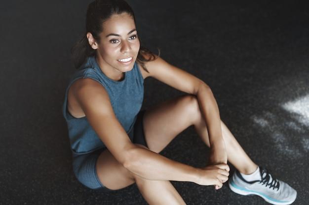 Sportvrouw overweegt venster tijdens het rusten in de sportclub