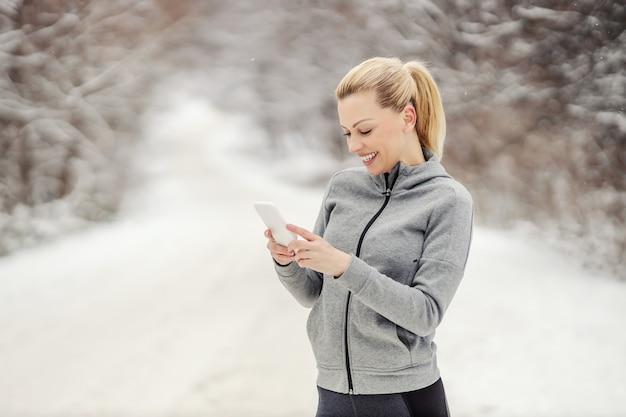 Sportvrouw permanent in de natuur op besneeuwde winterdag en sms-bericht.