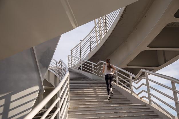 Sportvrouw rent de trap op