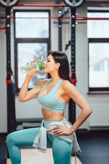 Sportvrouw rusten en drinkwater op trappen in de sportschool