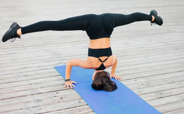 Sportvrouw staat op haar hoofd op een yogamat en spreidt haar benen met spleten op houten planken buitenshuis