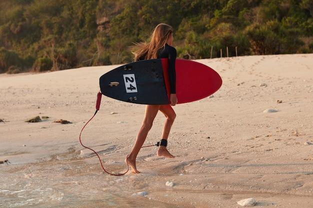 Sportvrouw tevreden met goede weersomstandigheden bont surfen, loopt op nat zand in de buurt van de oceaan
